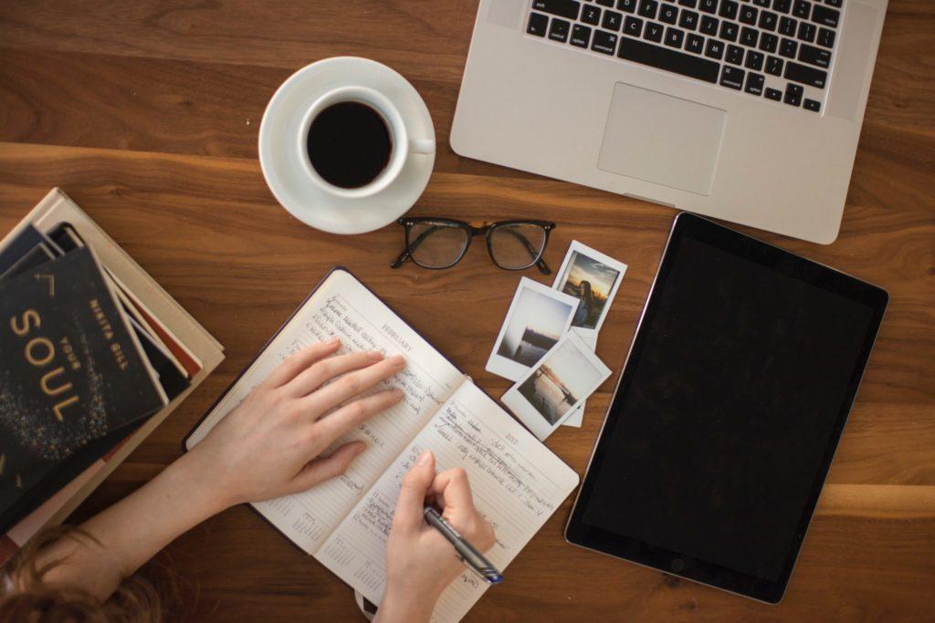 table-with-book-laptop-mug-photos-ontop