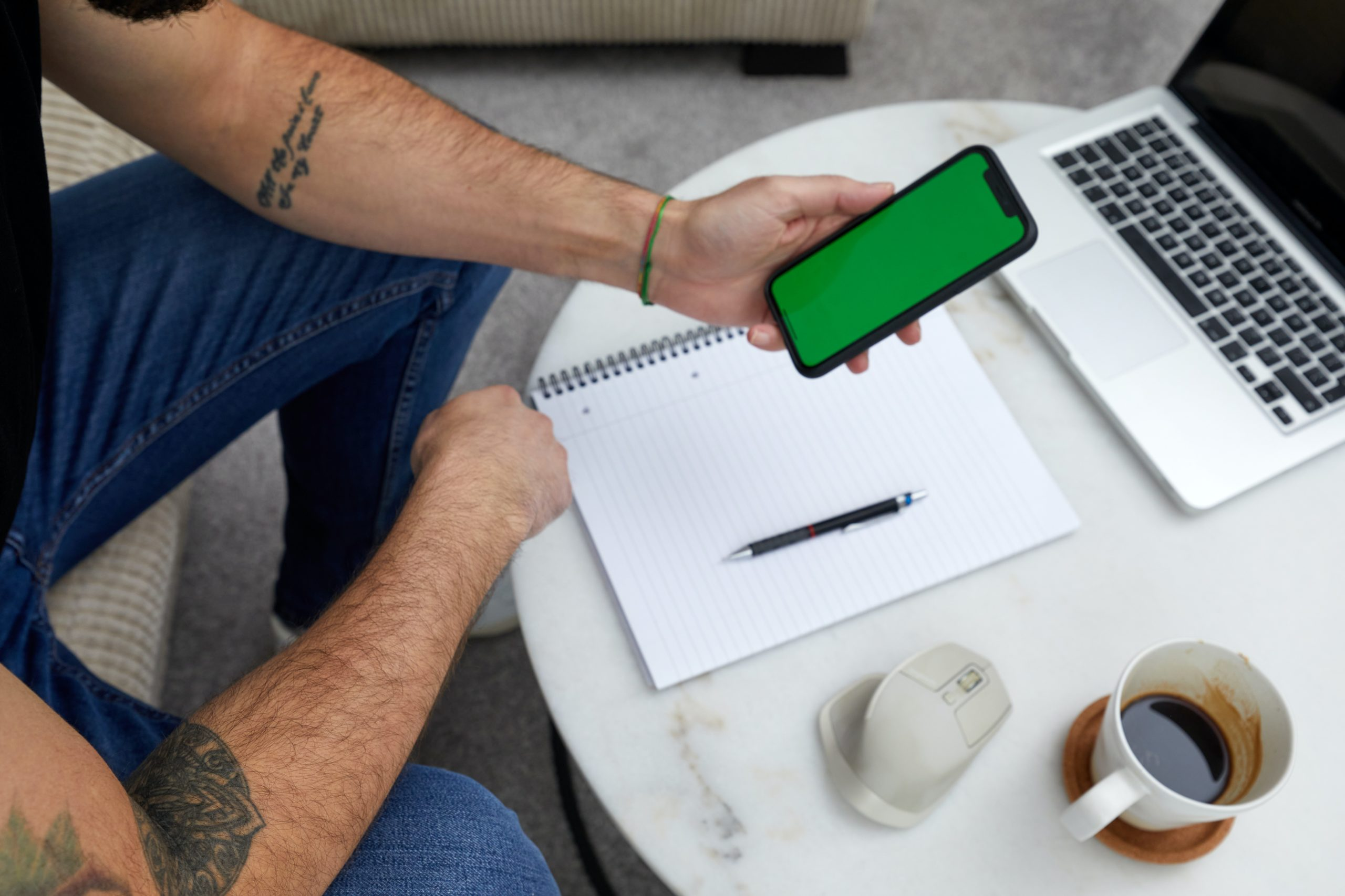 Man holding smartphone with laptop in the background