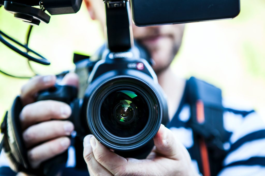 Man filming on video camera using video content as the best way to advertise your business