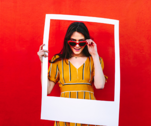 Woman in a yellow dress holding an Instagram cut out