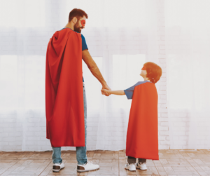 A Father and son wearing red superhero masks and capes