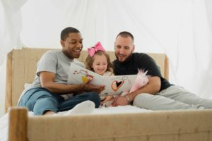 Two men in dark tshirts sitting on a bed with a girl dressed in pink reading a book