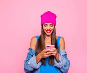 A female wearing a blue top and pink beanie on her smartphone against a pink background