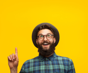 A man wearing a checked shirt, a hat and glasses point to the ceiling on a yellow background
