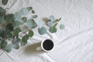 A coffee mug and penny gum on a bed sheet