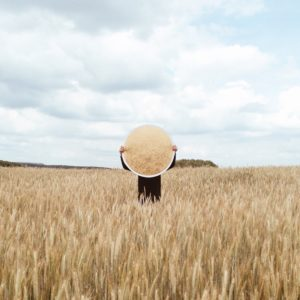 A person standing in a wheat field with a reflector