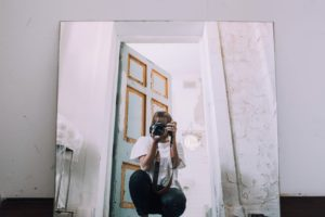 A female photographer taking a picture of herself in a mirror