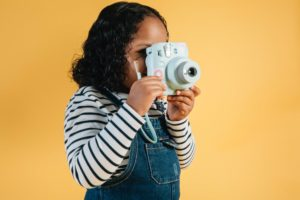 A girl taking a picture on a polaroid camera