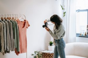 A woman taking pictures of clothing with natural light