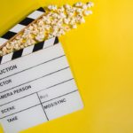 A clapperboard with popcorn on a yellow background showing how to host your first webinar