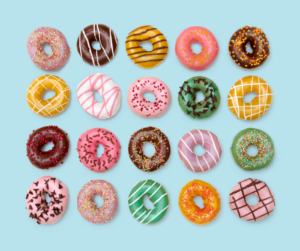Different colour donuts on a bright blue background used to plan an Instagram feed