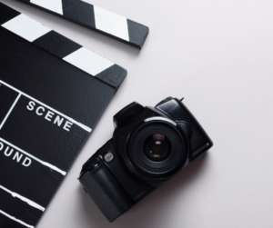 A camera and clapperboard on a light background