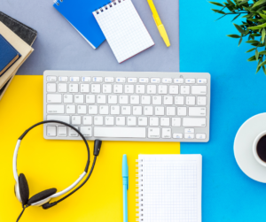 Headphones, a keyboard, pens and a notepad on a yellow and blue background