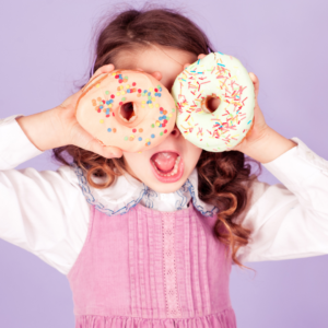 A girl holding two donuts up to her eyes
