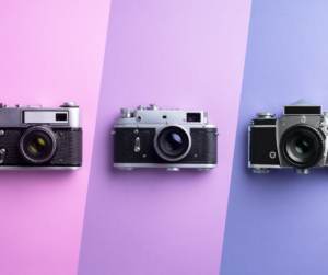 Three cameras on a purple background