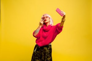 A female influencer in a pink jersey taking a selfie on a yellow background