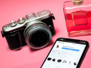 A picture of a smartphone, camera and perfume on a pink background