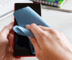 A person cleaning their phone lens