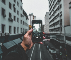 A person taking a picture of a building using the panoramic feature as a smartphone photography tip