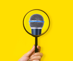 A magnifying glass over a microphone on a yellow background