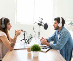 Two people sitting at a table recording a podcast like a pro