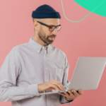 A man on his laptop against a pink background